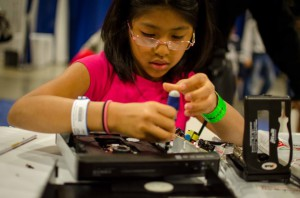 Girl repairing a DVD player at the USA Science & Engineering Festival. Photo by iFixit.
